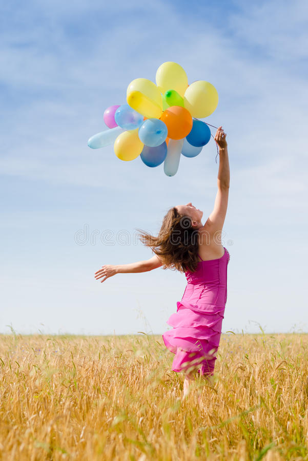 Portrait of having fun romantic blond young lady holding air balloons in the field on summer blue sky outdoors stock image