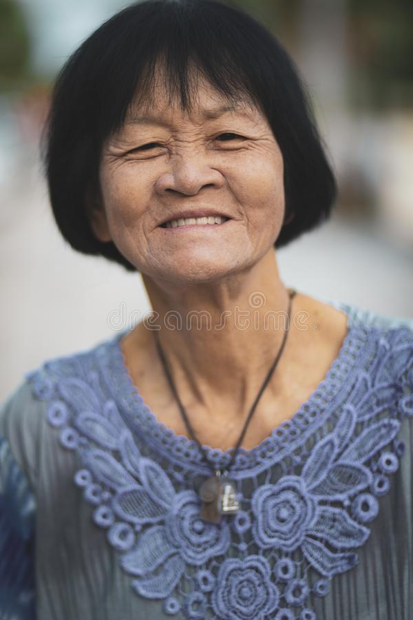 Portrait headshot of old asian woman toothy smiling face royalty free stock photography