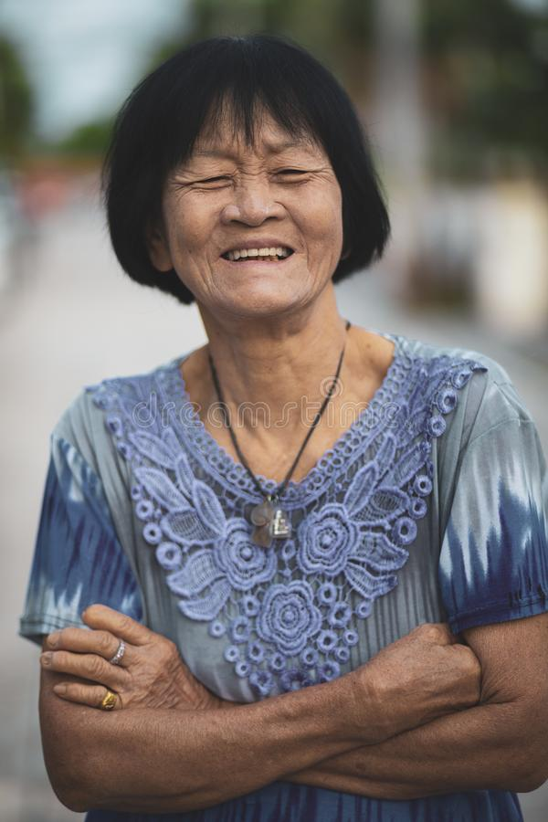 Portrait headshot of old asian woman toothy smiling face royalty free stock photo