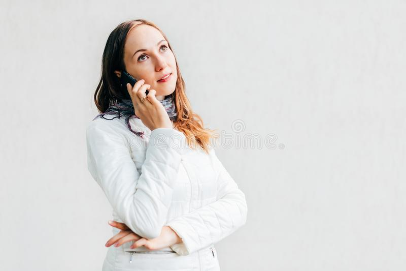 Portrait headshot of young woman looking away thoughtfully and talking on mobile phone royalty free stock photography