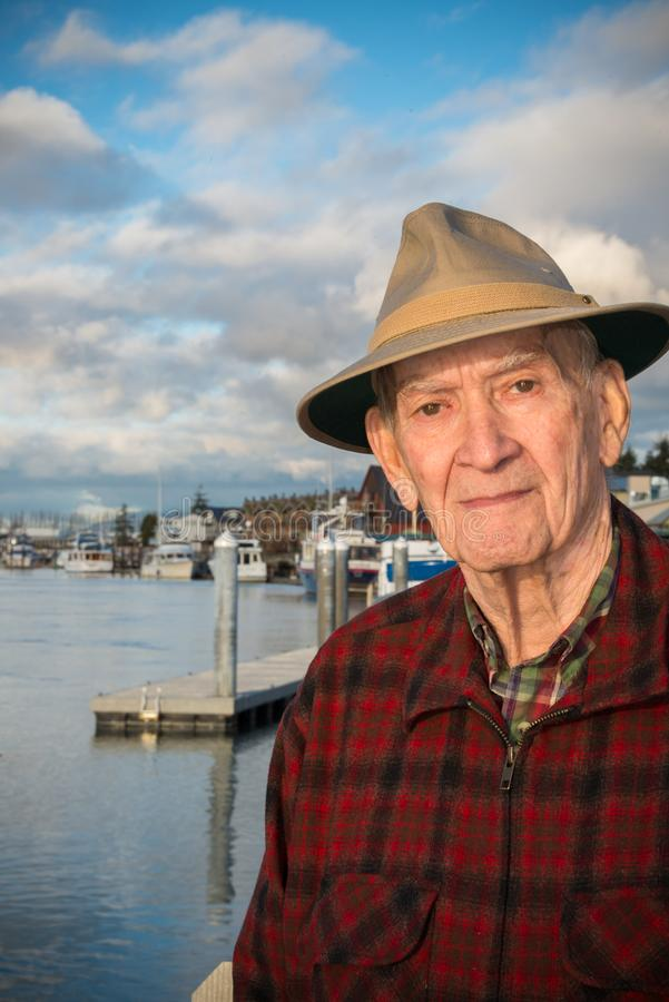 Portrait healthy active mature man by marina. Vertical. Portrait of a healthy, active male senior dressed casually with hat with Boats Docket at Pier in the stock photography