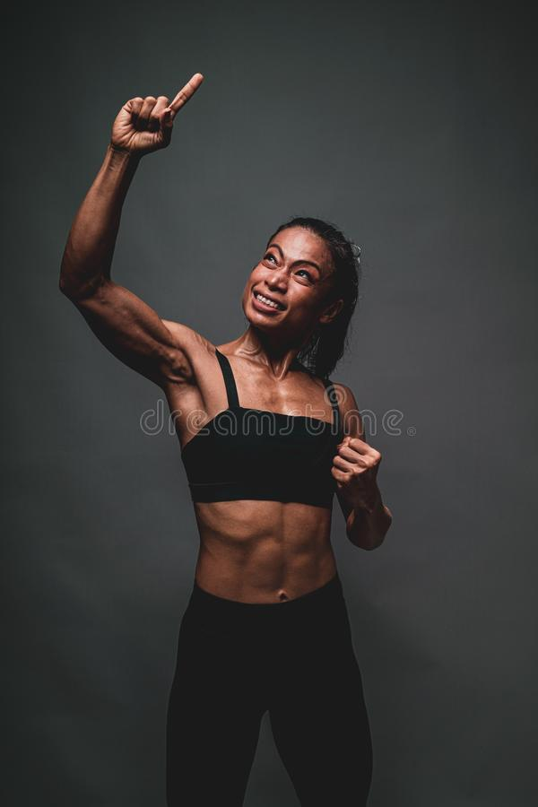 Portrait of healthy athletic 40 year old asian woman with a lean muscle and nice core body lifting her right arm and smiling with stock photography