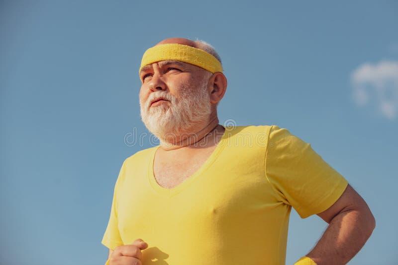 Portrait of healthy senior sport man jogger. Elderly man jogging. Senior man running in sunny nature. Healthy lifestyle stock image