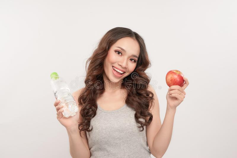 Portrait of a healthy woman with apple and bottle of water. Healthy fitness and eating lifestyle concept royalty free stock image