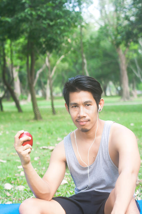 Portrait of healthy young man holding apple in nature royalty free stock images