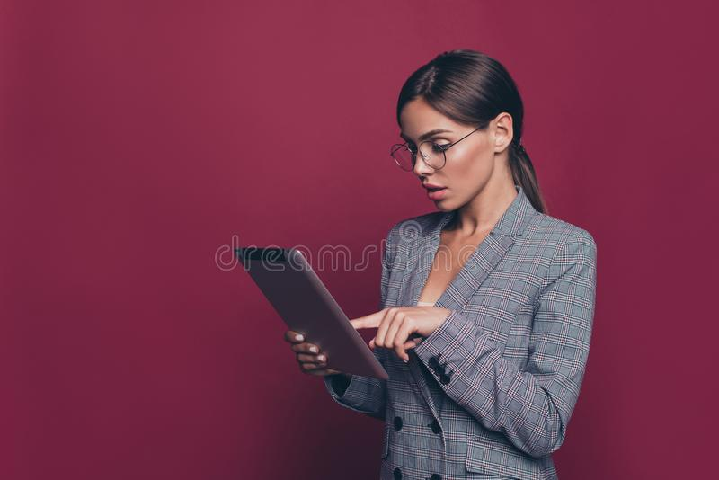Portrait of her she nice attractive lovely pretty classy focused lady professor ceo boss chief in gray checkered blazer. Holding in hands e-book  over maroon royalty free stock image