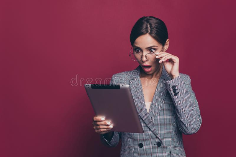 Portrait of her she nice attractive pretty classy wondered lady professor teacher lecturer in gray checkered blazer. Holding in hands e-book  over maroon royalty free stock image