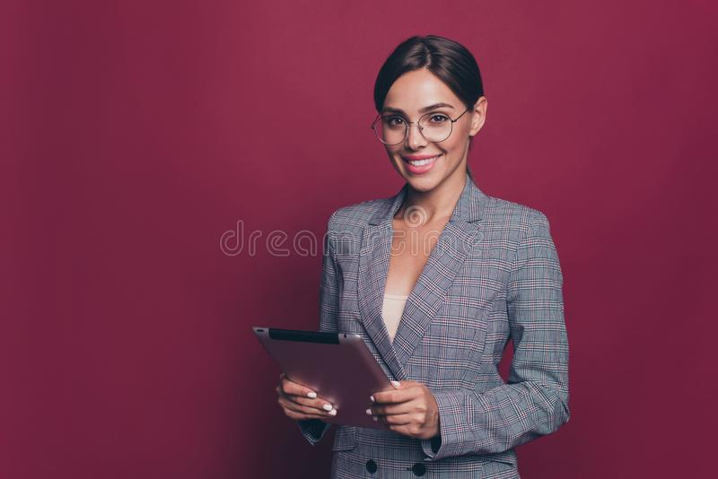 Portrait of her she nice cute attractive classy cheerful lady professor teacher lecturer tutor in gray checkered blazer. Holding in hands e-book  over maroon stock photo