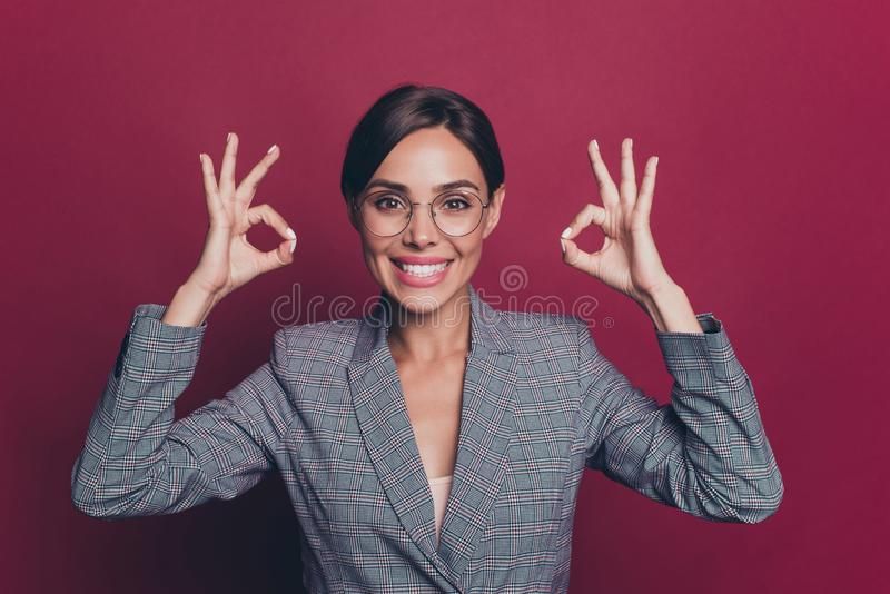 Portrait of her she nice cute attractive lovely sweet cheerful cheery optimistic lady wearing gray checkered blazer. Jacket showing double ok-sign  over maroon stock photography