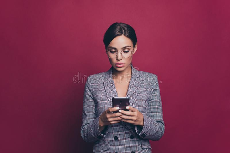 Portrait of her she nice cute attractive lovely sweet winsome classy chic focused concentrated lady wearing gray. Checkered jacket typing sms  over maroon royalty free stock photo