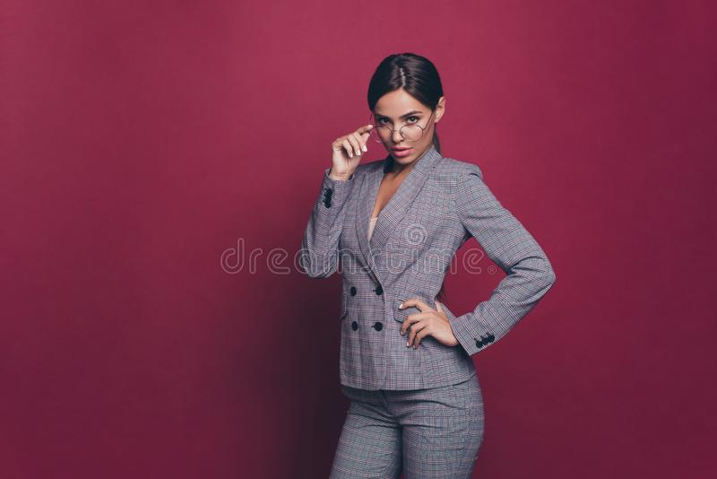 Portrait of her she nice cute chic classy attractive lovely charming fascinating lady wearing gray jacket suit blazer. Touching glasses  over maroon burgundy royalty free stock image
