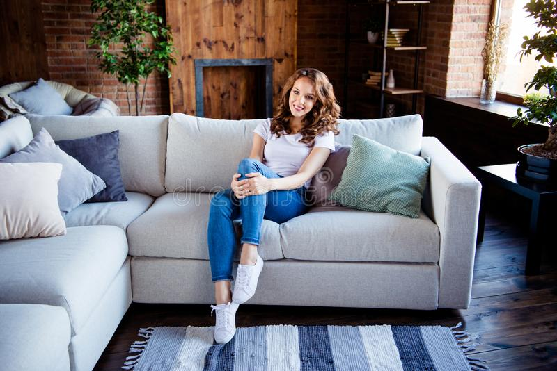 Portrait of her she nice-looking attractive lovely charming stylish cheerful cheery lady sitting on comfortable sofa at stock photo