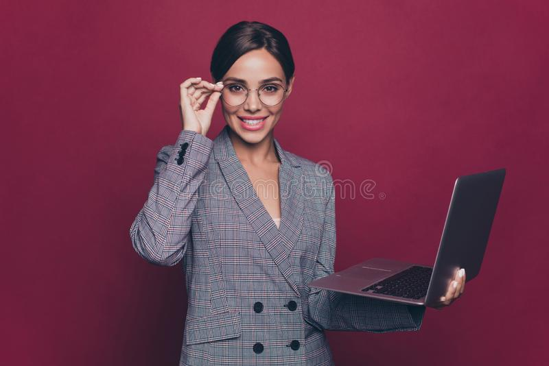 Portrait of her she nice pretty attractive lovely cheerful lady financier director wearing gray checkered blazer holding. In hands laptop isolated over maroon royalty free stock photography