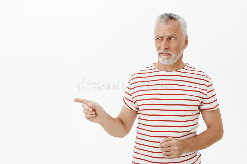 Portrait of hesitant doubtful and displeased intense senior man looking and pointing left suspicious with aversion and. Dislike staring at creepy thing stock photo
