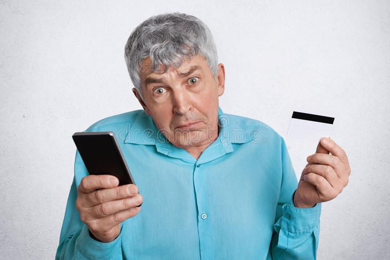 Portrait of hesitant grey haired mature male doesn`t know how to pay with credit card and make purchase online via internet with m. Obile phone, looks in royalty free stock images