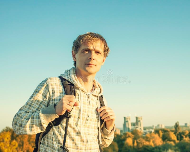 Portrait heureux colorized stylisé d'homme de vintage tenant le sac à dos et regardant le coucher du soleil photographie stock libre de droits