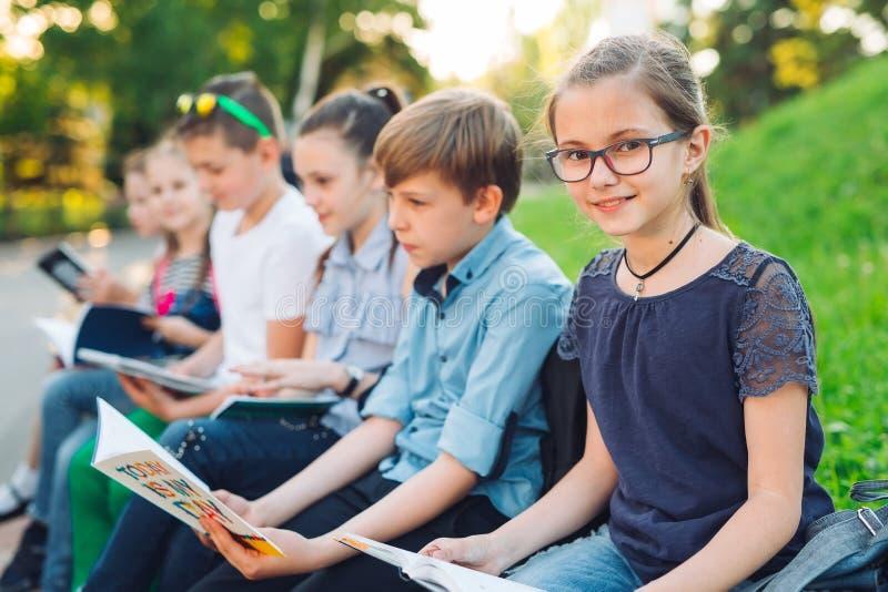 Portrait heureux de camarades de classe Camarades de classe asseyant avec des livres dans un banc en bois en parc de ville et étu photos libres de droits