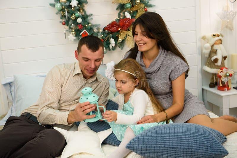 Portrait heureux de famille sur Noël, la mère, le père et l'enfant s'asseyant sur le lit et allumant une bougie à la maison, chri photographie stock libre de droits