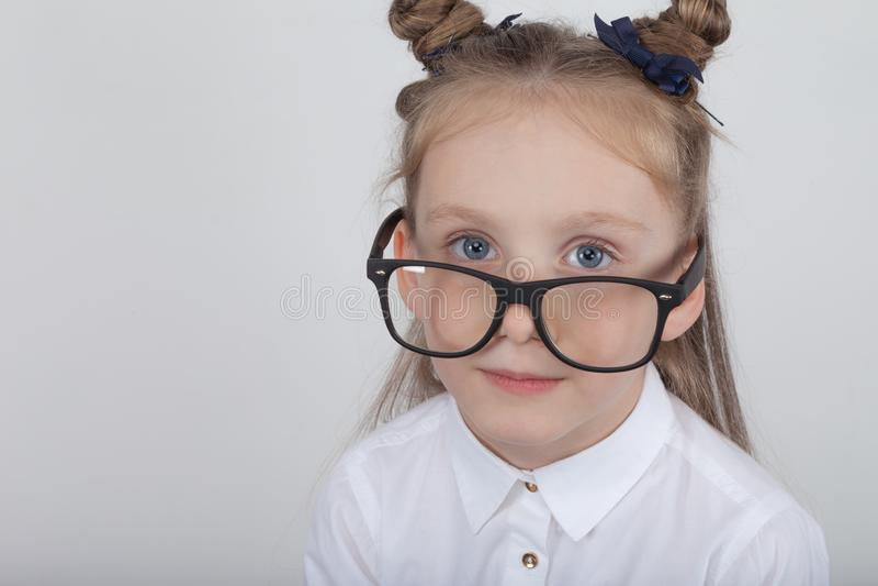 Portrait heureux de petite fille, chemisier blanc de port et lunettes noires de cadre, se tenant sur le fond en bois blanc De nou images stock