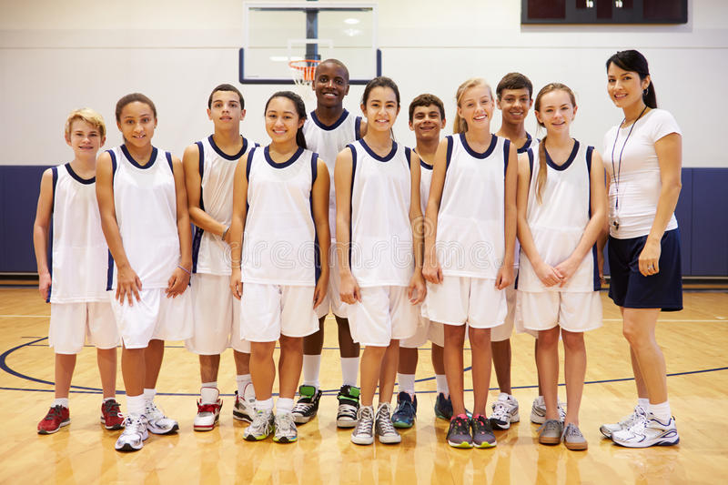 Portrait Of High School Sports Team In Gym With Coach. Looking At Camera Smiling royalty free stock image
