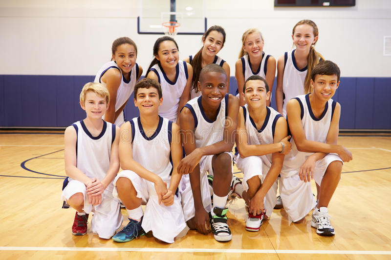 Portrait Of High School Sports Team In Gym. Kneeling Down Smiling stock images