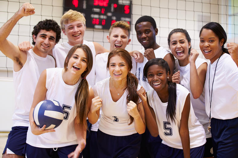 Portrait Of High School Volleyball Team Members With Coach. In Gymnasium Cheering stock image