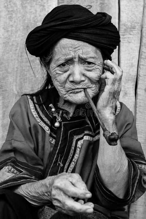 Portrait Of Hill Tribe Woman. 2010-07-25 in Phongsali, Laos: portrait in black and white of old hill tribe woman in traditional clothes smoking a pipe stock image