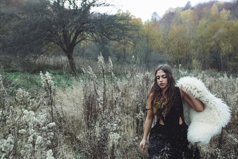 Portrait of a hippie girl in sheep`s clothing. A girl walks across the field and looks thoughtfully at the autumn grass. She is wearing a black dress and royalty free stock image