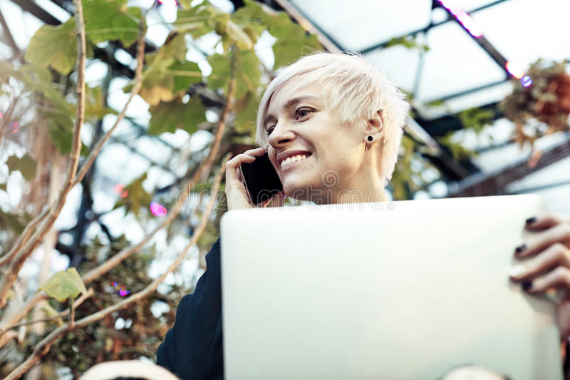 Portrait of hipster caucasian woman with blonde short hair talking by mobile phone. Smiling half-face face, Indoor botanical garde stock images