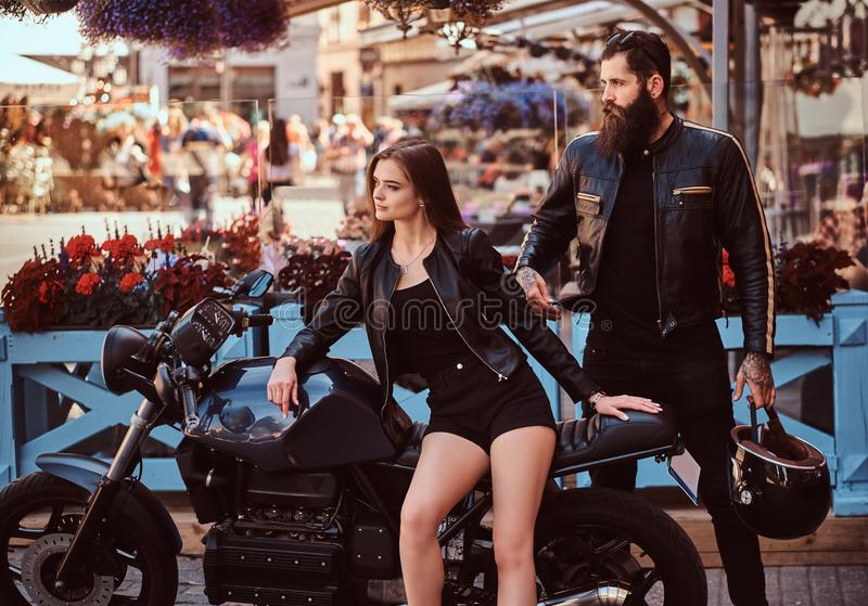 Portrait of a hipster couple - young sensual girl sitting on his custom-made retro motorcycle and a bearded brutal male royalty free stock image