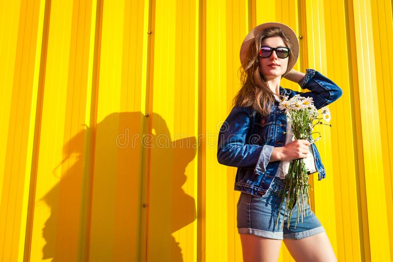 Portrait of hipster girl wearing glasses and hat with flowers against yellow background. Summer outfit. Fashion. Space royalty free stock images