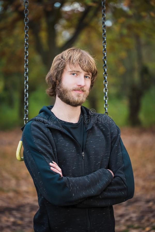 Portrait of an hipster sportive young man in the park royalty free stock photography