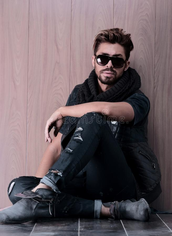 Casual young man with beard sitting on the floor stock photography