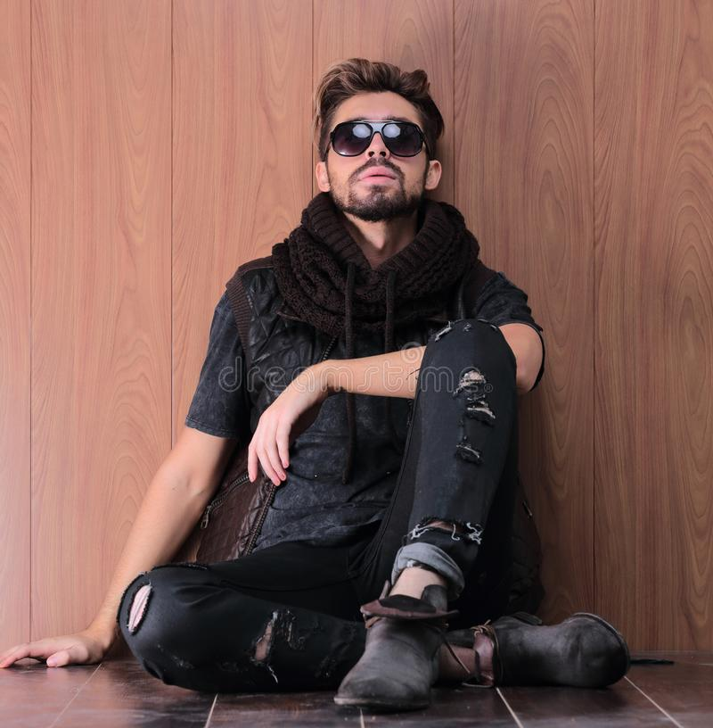 Casual young man with beard sitting on the floor royalty free stock image