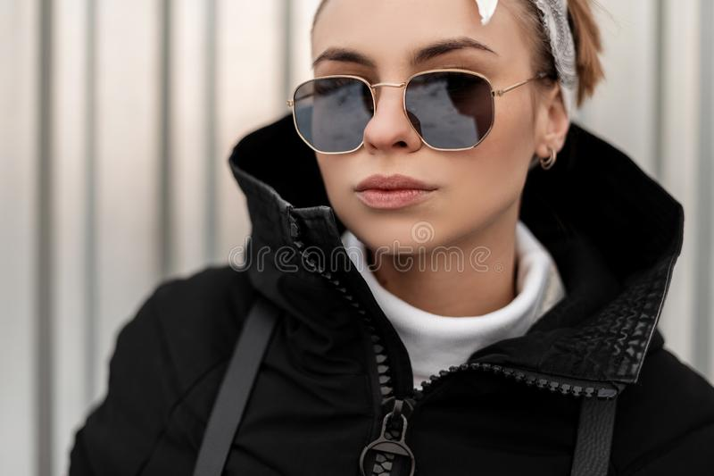 Portrait of a hipster young woman in stylish sunglasses in a bandana in a fashionable winter jacket near a gray metal wall. royalty free stock photo