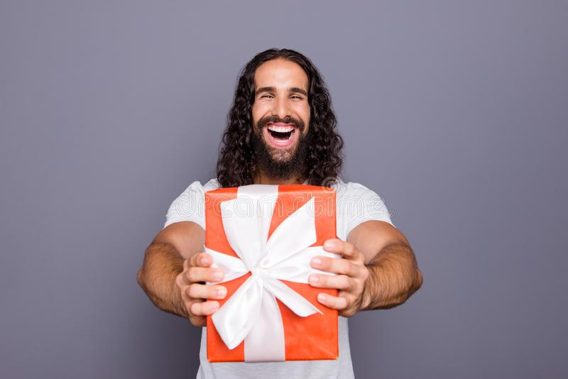 Portrait of his he nice attractive cheerful cheery ecstatic overjoyed wavy-haired guy giving you showing red gift box stock photography