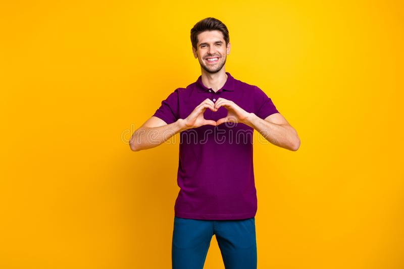 Portrait of his he nice attractive cheerful cheery guy wearing violet shirt showing heart symbol medical care isolated royalty free stock photo