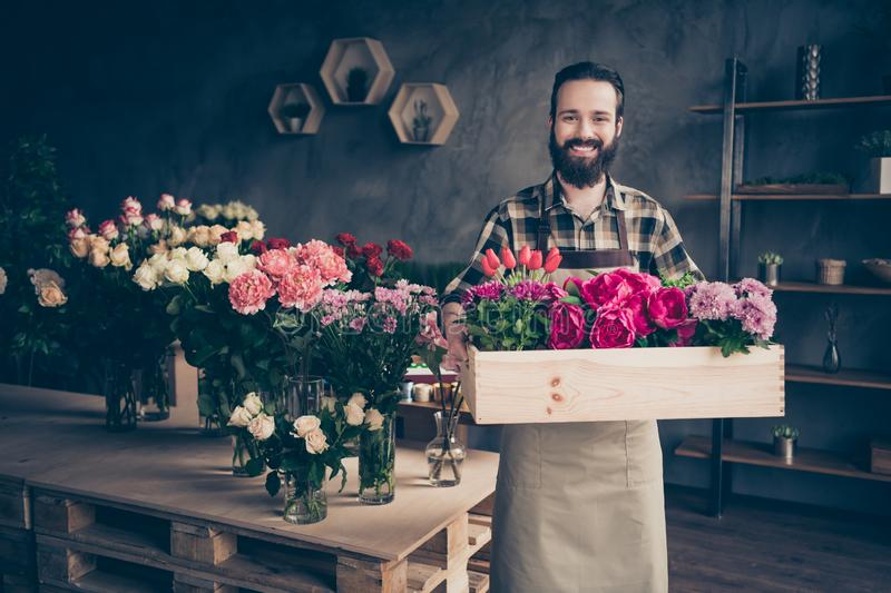 Portrait of his he nice attractive cheery cheerful content successful guy professional gardener holding big box peony royalty free stock photos