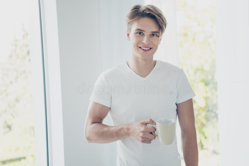 Portrait of his he nice attractive cute cheerful cheery guy drinking early morning sweet hot cacao at light white modern stock photos