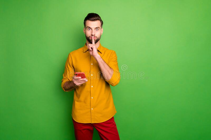 Portrait of his he nice attractive funky funny mysterious guy in formal shirt holding in hand cell showing shh sign. Portrait of his he nice attractive funky royalty free stock image