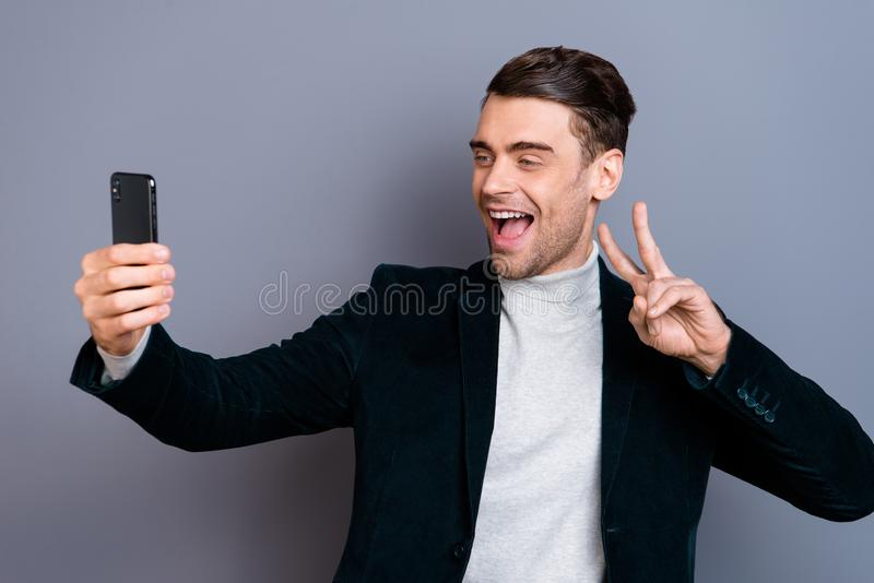 Portrait of his he nice attractive handsome bearded cheerful positive guy wearing velveteen blazer showing v-sign making. Taking selfie isolated over gray blue stock photos