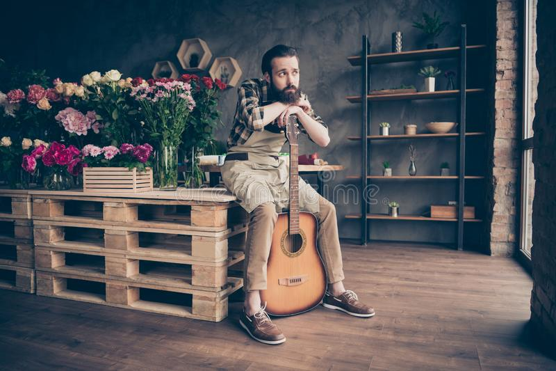Portrait of his he nice attractive sad gloomy grumpy poor disappointed guy gardener musician at modern industrial loft royalty free stock photography