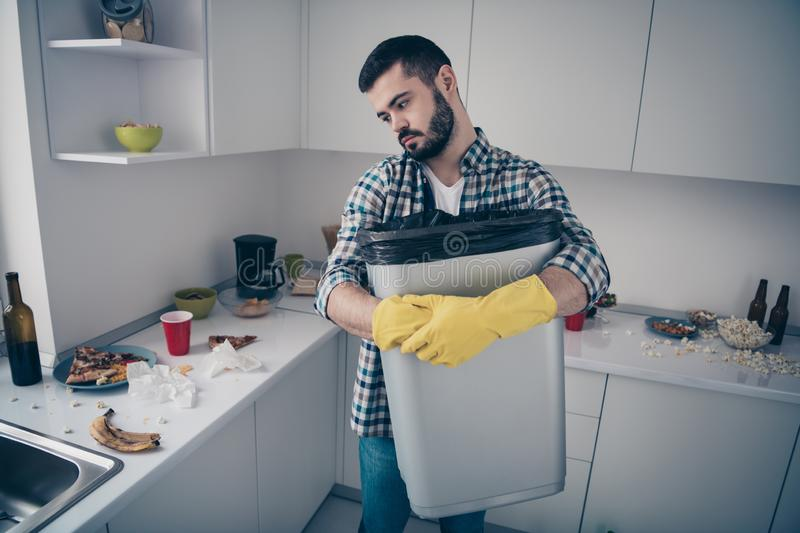 Portrait of his he nice attractive serious focused sad bored tired bearded guy wearing checked shirt doing domestic mess stock photo
