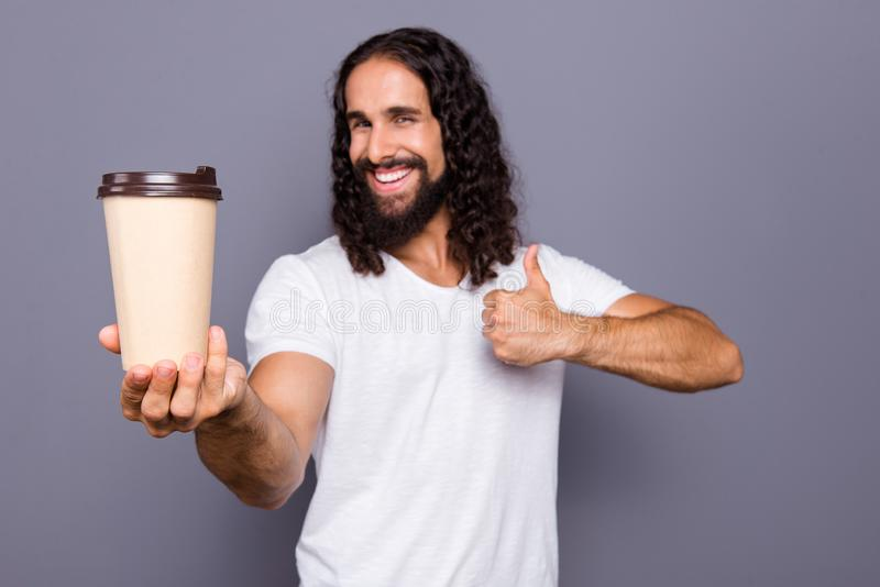 Portrait of his he nice cool attractive cheerful cheery wavy-haired guy giving takeaway cup showing thumbup isolated stock images