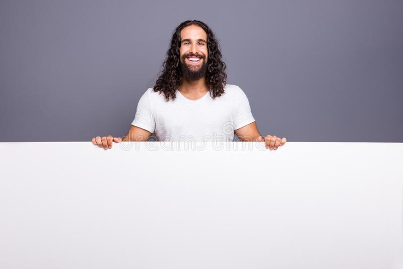 Portrait of his he nice handsome attractive cheerful cheery wavy-haired guy holding in hands empty copy space isolated stock photography