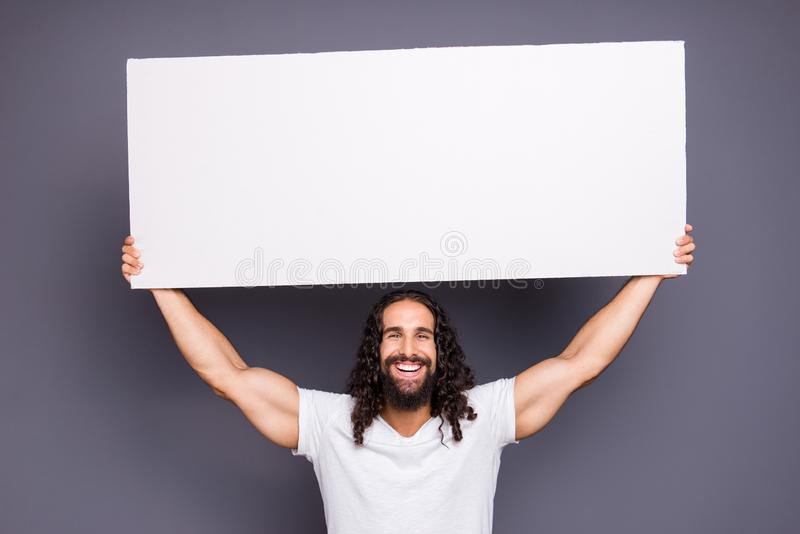 Portrait of his he nice handsome attractive cheerful sportive wavy-haired guy holding in hands large copy space novelty stock images