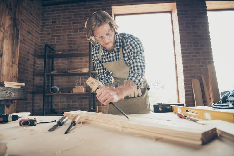Portrait of his he nice handsome blond focused guy artisan builder woodworker grinding hard wood at industrial brick stock images