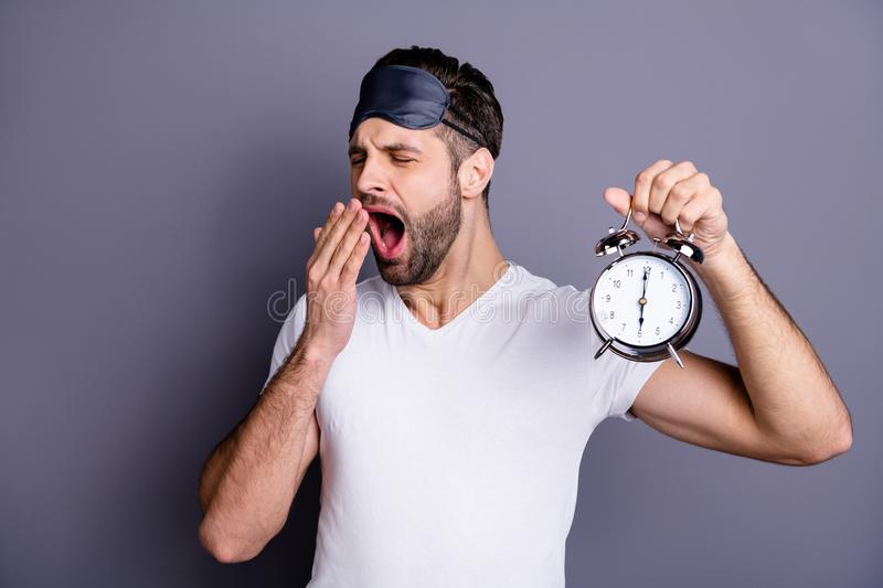 Portrait of his he nice-looking attractive tired bearded guy holding in hand clock waking up isolated over gray pastel royalty free stock images