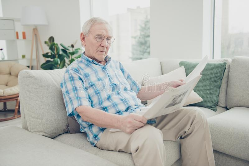 Portrait of his he single nice focused concentrated peaceful calm granddad sitting on divan reading world news paper in. Portrait of his he single nice focused stock images