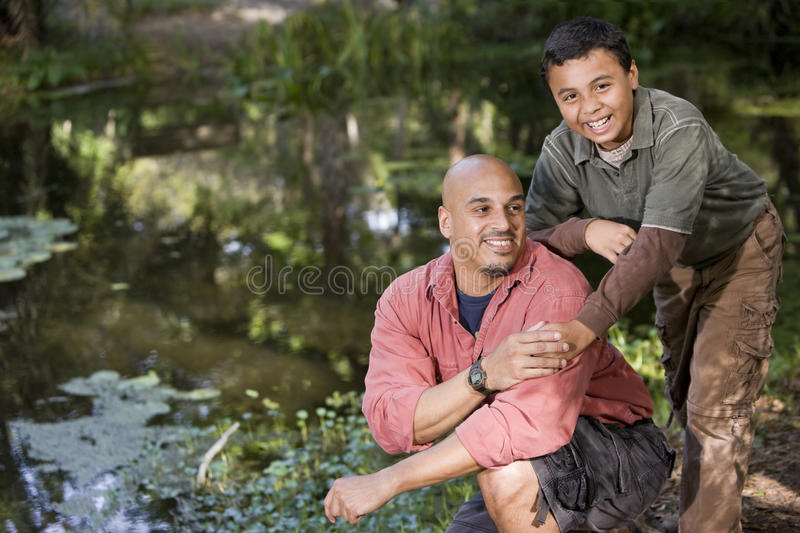 Portrait Hispanic father and son outdoors by pond royalty free stock image